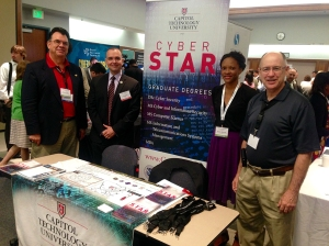 Capitol Technology University booth at CyberMontgomery 2015. Xavier A. Richards, Director of Graduate Recruitment, Paul de Souza, CSFI President and the Capitol Technology University educational crew.