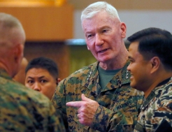 Lt. Gen. John Toolan, center, U.S. Commander of U.S. Marine forces in the Pacific, chats with Vice-Admiral Alexander Lopez, right, following the opening ceremony of their annual joint military exercise, dubbed Balikatan 2016 (Shoulder-to-Shoulder), Monday, April 4, 2016 at Camp Aguinaldo, in suburban Quezon city, northeast of Manila, Philippines. Toolan said that U.S. Defense Secretary Ash Carter would fly to the Philippines to witness some of the events of the 11-day exercises, which would see the deployment for the first time of a highly mobile rocket system that has been used in Afghanistan. The annual military drill, involving 5,000 U.S. personnel and 3,500 counterpart from the Philippines, is being conducted amidst tension in the South China Sea. (AP Photo/Bullit Marquez)